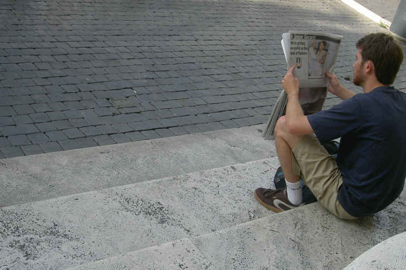 A man reading the newspaper while seated on steps in Rome
