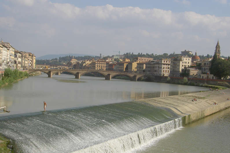 A Man Walking Along the Top of One of the Arno River Dams in Florence