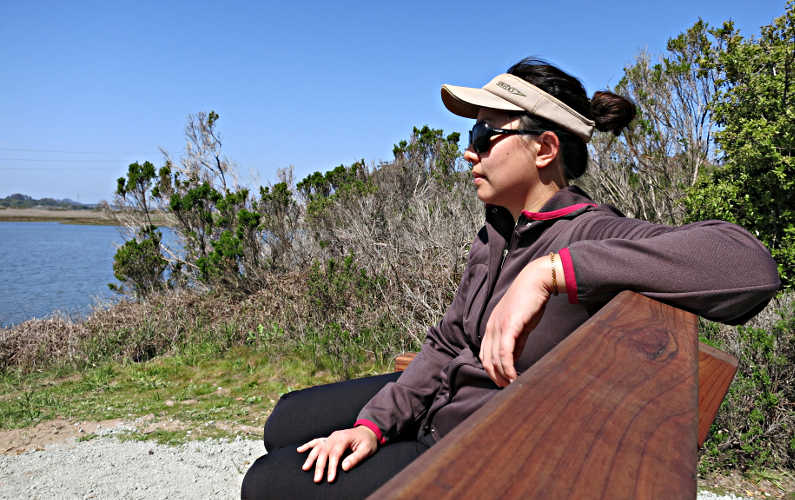 Nadia is Sitting on a Wooden Bench at Elkhorn Slough
