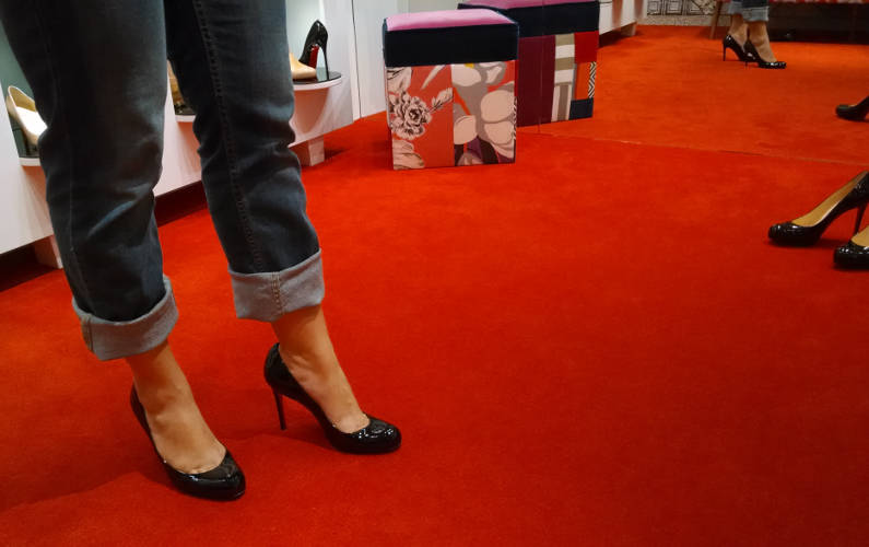 Nadia Trying on Christian Louboutin Black Pumps by a Mirror with Other Models She Has Tried On