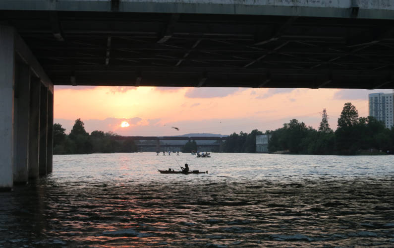 View of the Austin Sunset and a Person in a Boat Under a Bridge During the Lone Star Riverboat Tour