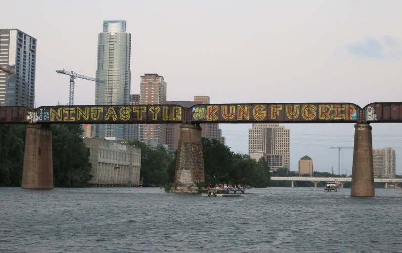 Train Bridge with Graffiti Art During the Lone Star Riverboat Tour