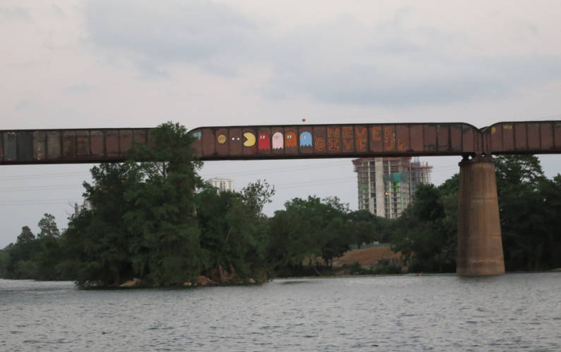 Train Bridge with Pac Man Graffiti Art During the Lone Star Riverboat Tour