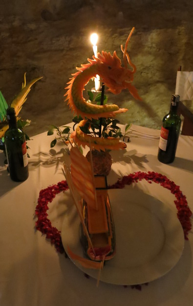 Candle Lit Vegetable Carved Dragon and Chinese Junk Boat Displayed at Indochina Junk Cave Dinner