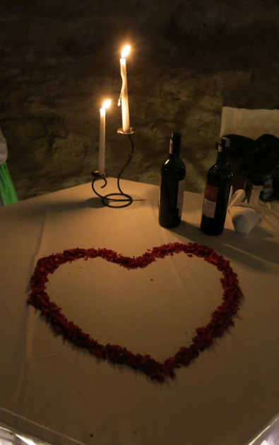 Candle Lit 2 Bottles of Wine and a Flower Petal Shaped Heart Displayed at Indochina Junk Cave Dinner