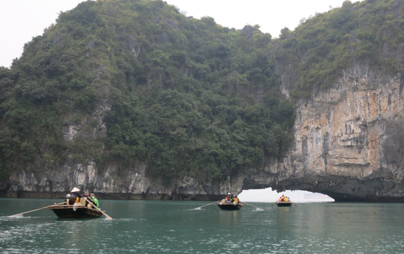 Several Boats of Guests Taken Toward Opening in Rock Formation at the End of the Indochina Junk Tour