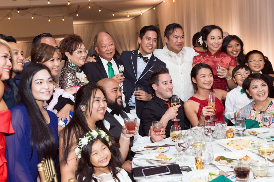 JM and Nadia posing with a table of guests