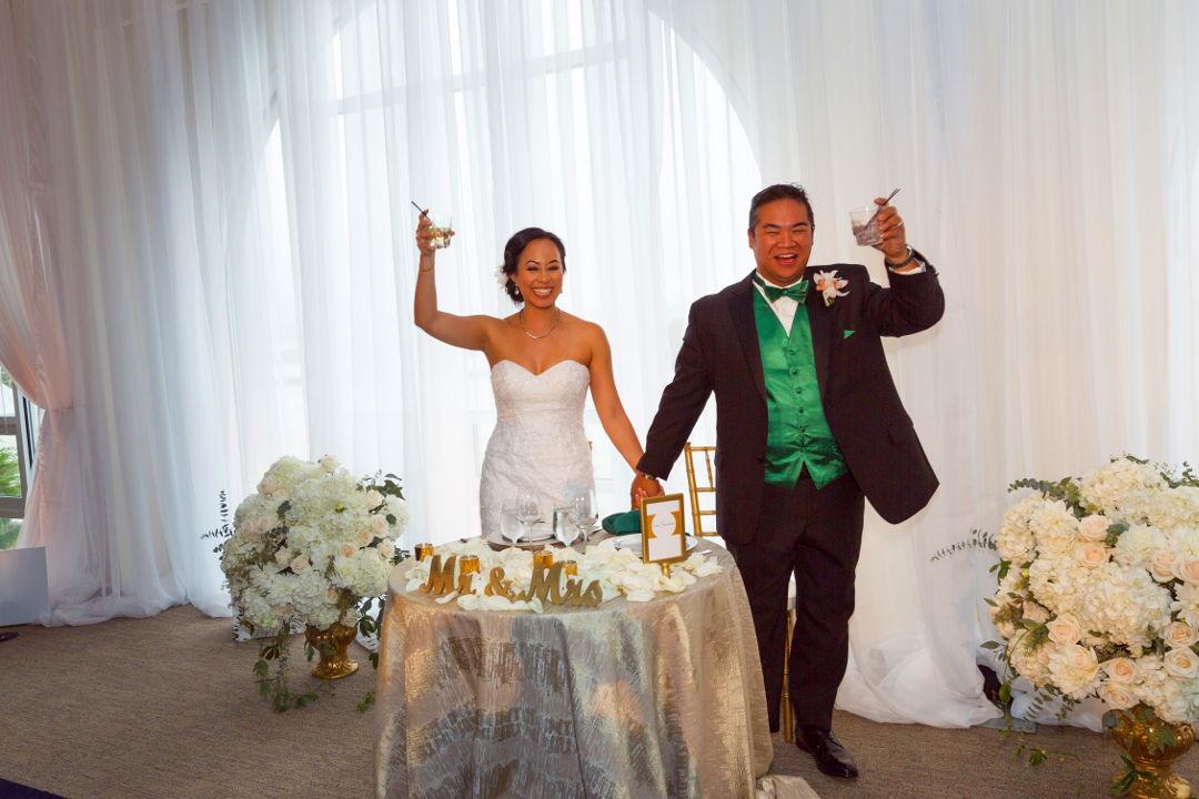 Nadia and JM toasting with raised glasses