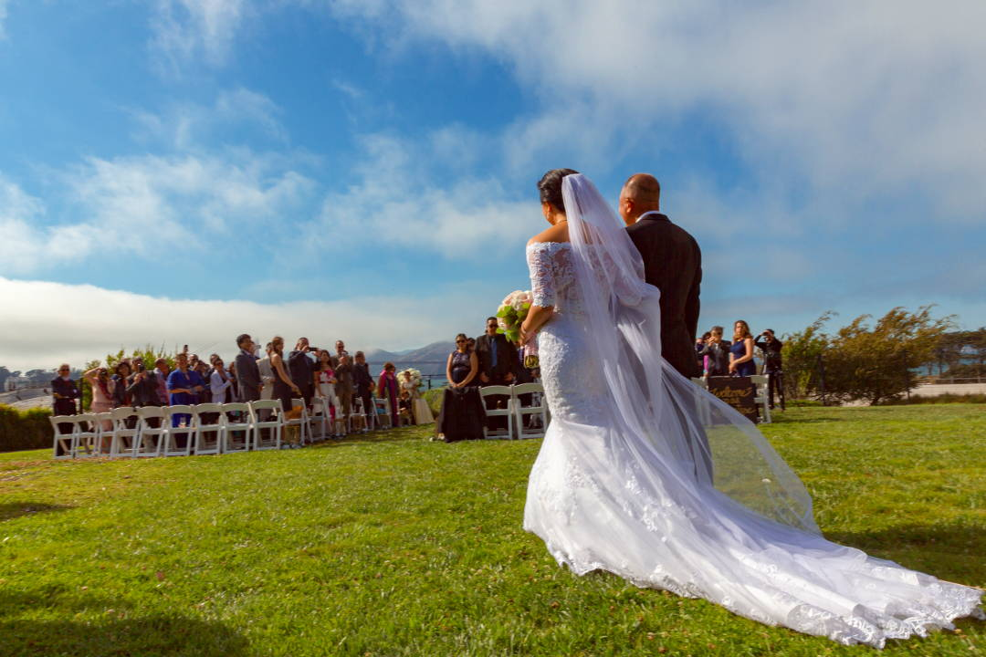 Nadia being walked down the grass toward JM to be married at the Presidio