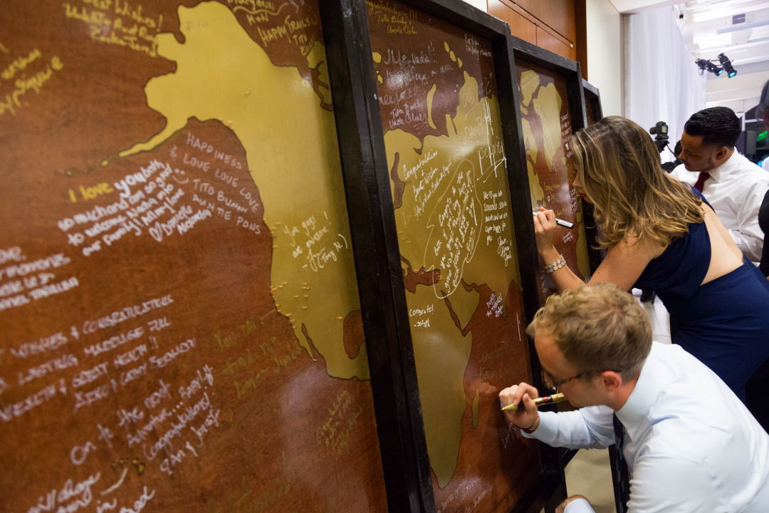 Wedding guests writing on the world map