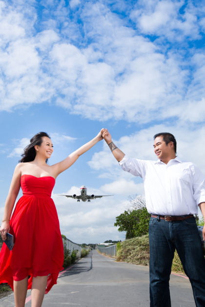 Nadia in a Red Dress Holding Hands with JM with a Plane Landing in the Background at Taipei Songshan Airport By Ching Hua