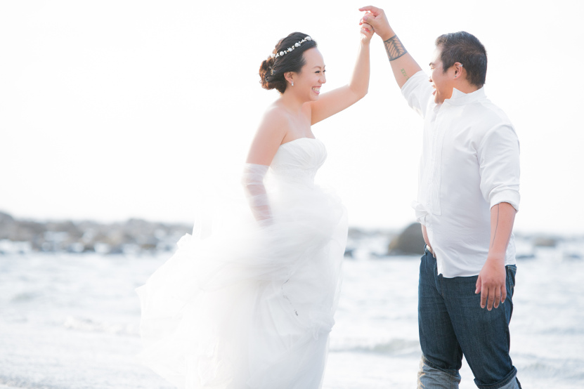 Barefoot Nadia in a Flowing White Wedding Dress Being Spun By JM in a White Tuxedo Shirt and Dark Blue Jeans on the Beach by Ching Hua Bridal Art