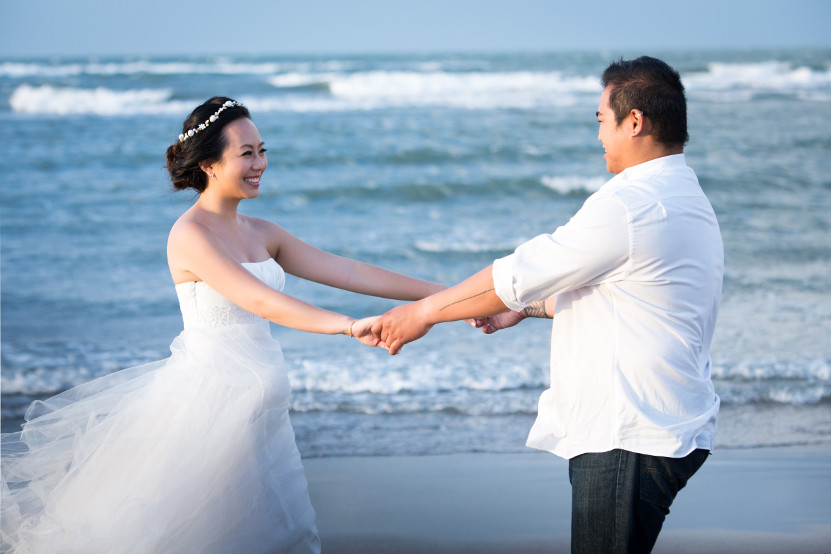 Barefoot Nadia in a White Wedding Dress Hand in Hand with JM in a White Tuxedo Shirt and Dark Blue Jeans on the Beach by Ching Hua Bridal Art