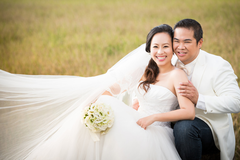 Nadia in a White Wedding Dress Being Held by JM in a White Tuxedo Jacket and Dark Blue Jeans While Seated in the Grass by Ching Hua Bridal Art