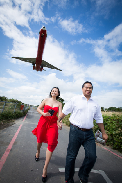 Nadia in a Red Dress Hand in Hand with JM Below a Plane at Taipei Songshan Airport By Ching Hua