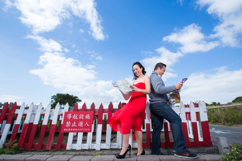 Nadia in a Red Dress and JM in a Grey Sweater Back to Map Looking at Maps at Taipei Songshan Airport By Ching Hua