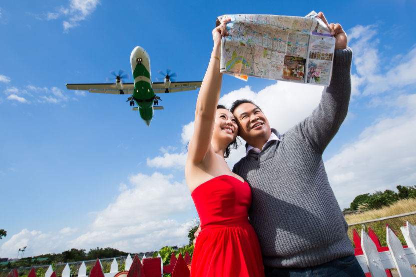 Nadia in a Red Dress and JM in a Grey Sweater Holding Up a Map with a Place Landing in the Background Nadia Holding Hands with JM with a Plane at Taipei Songshan Airport By Ching Hua