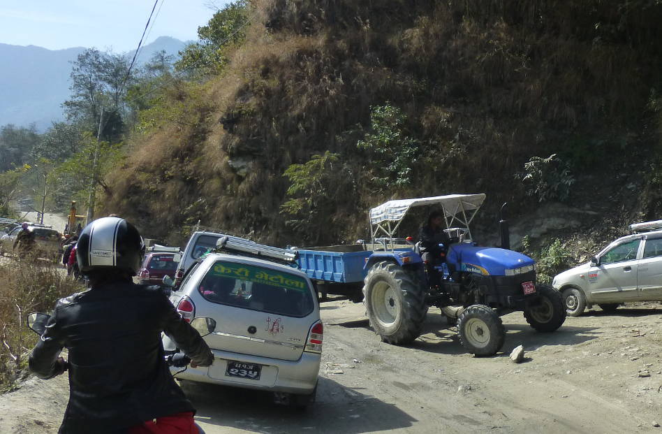 Motorcycle, Cars and a Tractor Contributing to Heavy Traffic in the Mountains of Nepal