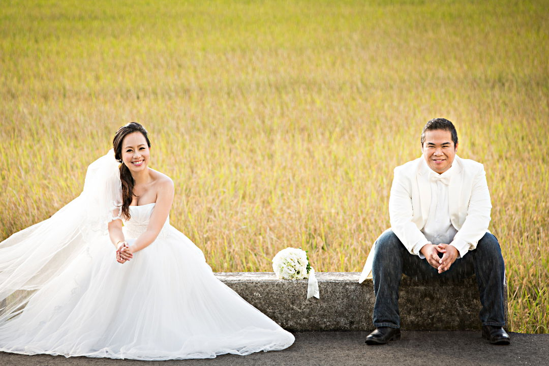 Nadia in a White Wedding Dress Seated with a Bouquet Next to JM in a White Tuxedo Jacket and Dark Blue Jeans by Ching Hua Bridal Art