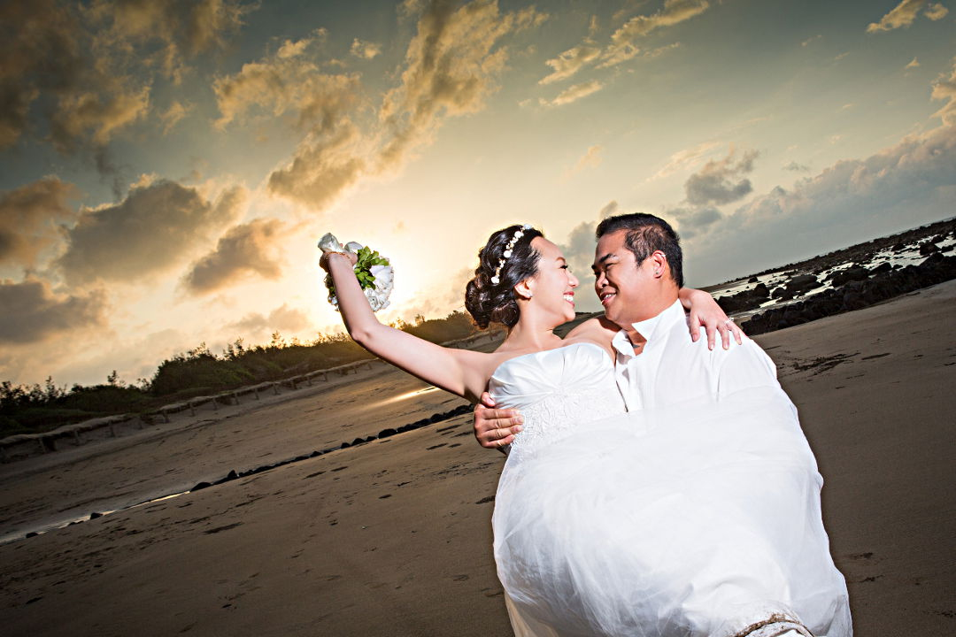 Barefoot Nadia in a White Wedding Dress and a Bouquet Being Carried by JM in a White Tuxedo Shirt and Dark Blue Jeans During Sunset on the Beach by Ching Hua Bridal Art