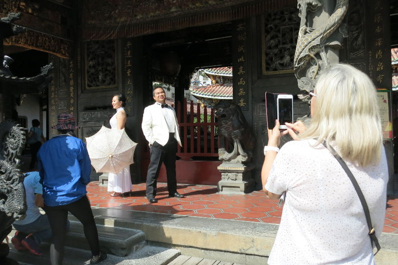 Ching Hua Bridal Art Behind the Scenes at the Temple with Nadia and JM Having Their Photo Taken by a Tourist