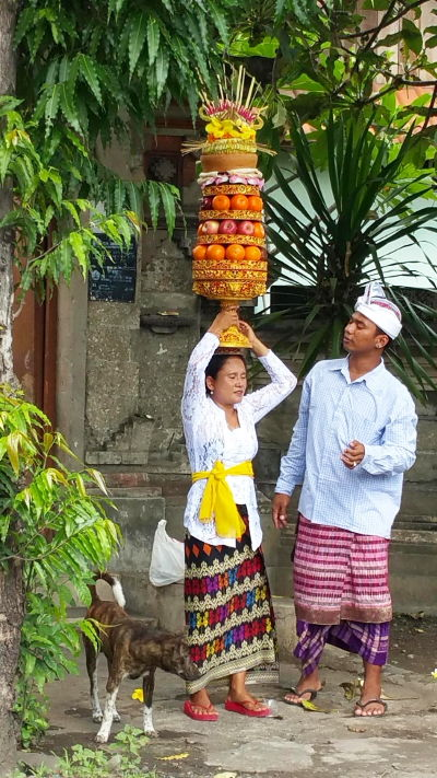 Balinese Man with a Woman Balancing Tower of Offerings on Her Head