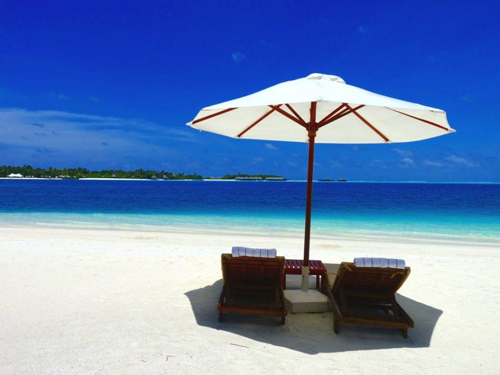 Beach Loungers Under an Umbrella on the Conrad Maldives Beach
