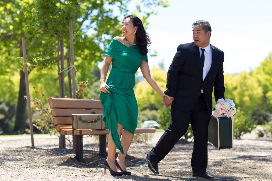 JM and Nadia running away with suitcases and flowers in Los Gatos Vasona Park