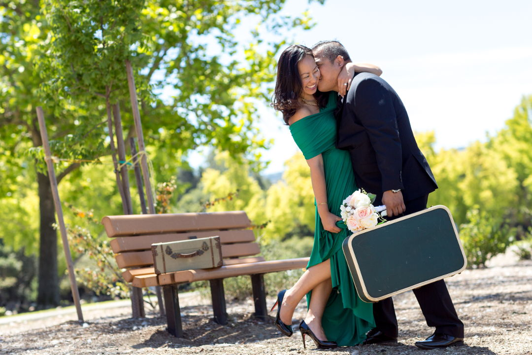 Jm and Nadia posing with suitcases and flowers in Los Gatos Vasona park