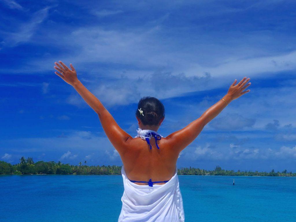 Nadia posing overlooking the ocean and islands of Huahine