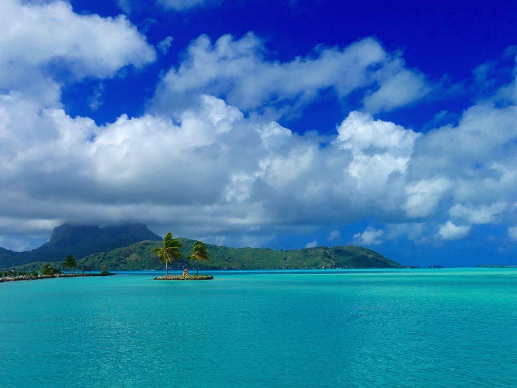 Palm trees and clouds over island of Bora Bora