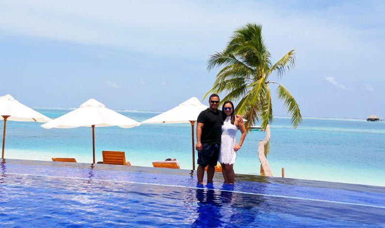 Nadia and JM Posing on the Edge of the Conrad Maldives Infinity Pool Next to the Lone Palm Tree