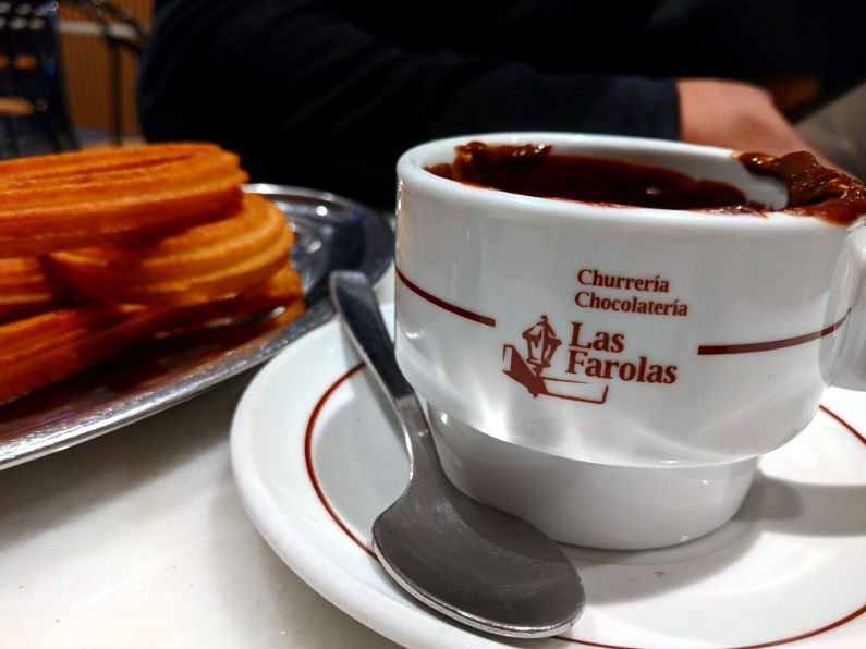 Churrería-Chocolatería Las Farolas Close Up of Cup of Chocolate Next to Churro Stack