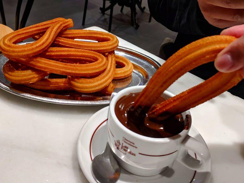 Churrería-Chocolatería Las Farolas Dipping Churro into Chocolate in Front of Stack of Churros